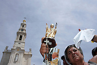 Pilgrim hold the  statue and picture of the Pope John Pual II  during the procession  of Fatima in central Portugal .Thousands of pilgrims converged on Fatima Santuary to celebrate the anniversary of the Fatima miracle when three shepherd children claimed to have seen the Virgin Mary in May 1917. Reportedly the aparition of a shining lady told the children - Lucia, Francisco, and Jacinta - to meet her in the same place on the 13th day of each month until October.