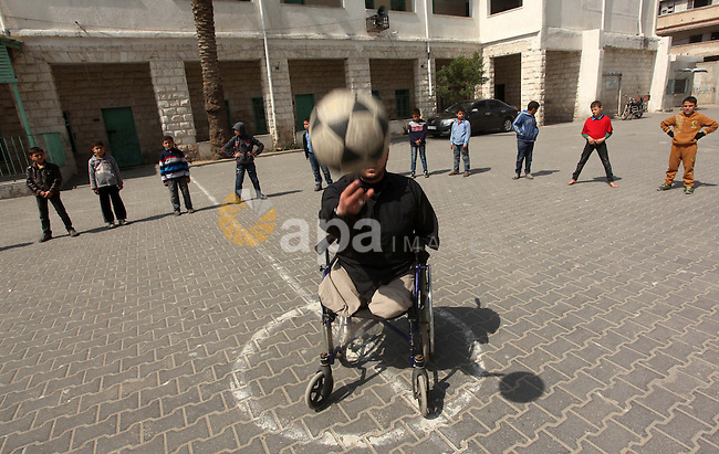 Wheelchair-bound Palestinian student teacher Ahmed al-Sawaferi, 25, who said that he lost his both legs and his left arm in an Israeli air strike in 2008, plays with a student  at an elementary school in Gaza City March 19, 2015. Al-Sawaferi, a father for two children, is due to hold a B.A in Islamic studies after finishing his last university semester in June this year. Photo by Ashraf Amra