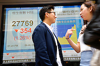 HONG KONG - MAY 05: Beverly Chung and Keith Cheung chat in front of a stock exchange board displaying the Hong Kong index (Hang Seng index) in Central business district, on May 5, in Hong Kong. (Photo by Lucas Schifres/Pictobank)
