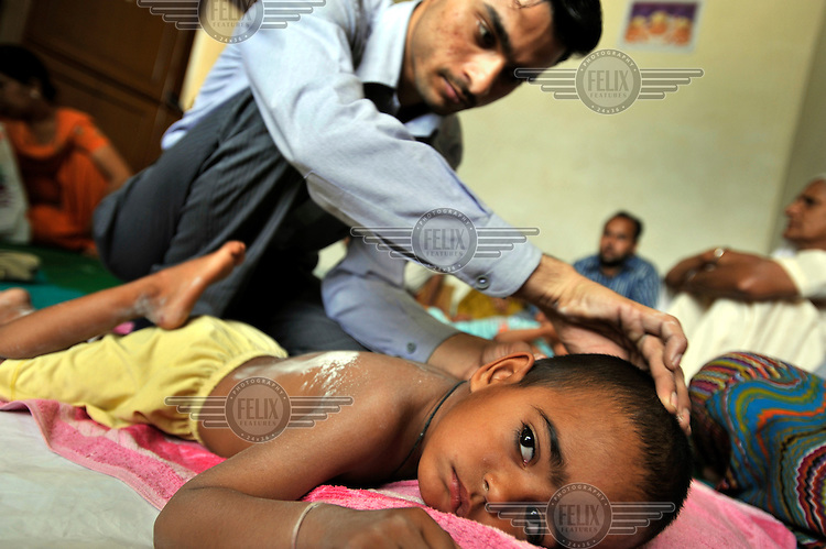5 year old Ravneet who has birth defects is treated by a doctor at the privately funded Baba Farid Centre in Faridkot. An increasing and ignored percentage of children are being born suffering the side effects of industrial pollution. The Baba Farid Centre was set up by Dr Pritpal Singh and is staffed on a volunteer basis by his network of similarly concerned fellow junior doctors and specialists. It treats its patients with a mixture of homeopathic, ayurvedic and acupuncture methods.