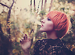 Profile portrait of a young female with short orange hair and dark make up, looking away from the camera, blowing out cigarette smoke and holding a cigarette in her hand, with forest background.
