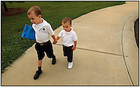 An older brother leads his younger brother into school. Photo is model released and can be used to illustrate other purposes. Name of school can be removed from shirt.