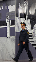 "Moscow, Russia, 20/06/2010..A policeman walks past murals depicting Raskolnikov's double murder and Svidrigailov's suicide in Crime & Punishment at the just-opened Dostoevsky metro station, the newest in Moscow's underground metro system. The station's opening was delayed by several weeks after psychiatrists claimed the gloomy and violent images in murals depicting scenes from Dostoevsky's novels would make the station a ""mecca for suicides""."