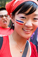 South Korea fan Shin Park shows off her colors while watching her team play against France on June 18, 2006 on a giant outdoor television in a section of New York City known as &quot;Korea Way&quot;.<br /> <br /> The World Cup, held every four years in different locales, is the world's pre-eminent sports tournament in the world's most popular sport, soccer (or football, as most of the world calls it).  Qualification for the World Cup is open to any country with a national team accredited by FIFA, world soccer's governing body. The first World Cup, organized by FIFA in response to the popularity of the first Olympic Games' soccer tournaments, was held in 1930 in Uruguay and was participated in by 13 nations.    <br /> <br /> As of 2010 there are 208 such teams.  The final field of the World Cup is narrowed down to 32 national teams in the three years preceding the tournament, with each region of the world allotted a specific number of spots.  <br /> <br /> The World Cup is the most widely regularly watched event in the world, with soccer teams being a source of national pride.  In most nations, the whole country is at a standstill when their team is playing in the tournament, everyone's eyes glued to their televisions or their ears to the radio, to see if their team will prevail.  While the United States in general is a conspicuous exception to the grip of World Cup fever there is one city that is a rather large exception to that rule.  In New York City, the most diverse city in a nation of immigrants, the melting pot that is America is on full display as fans of all nations gather in all possible venues to watch their teams and celebrate where they have come from.