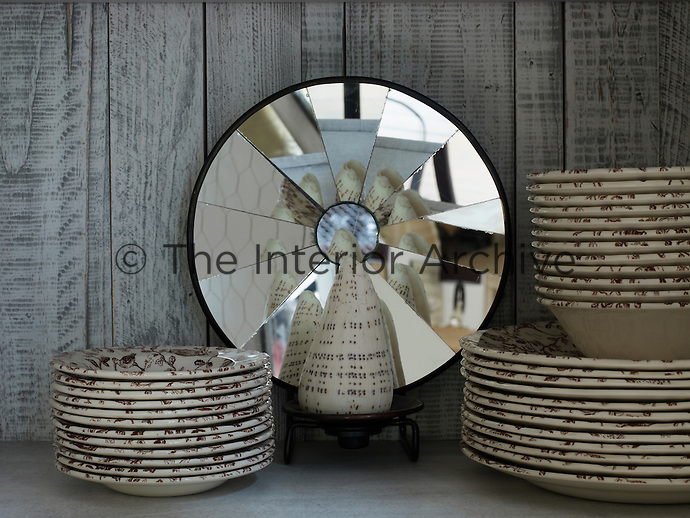 Brown and white plates and bowls are stacked on a shelf in a built-in cupboard in the dining room