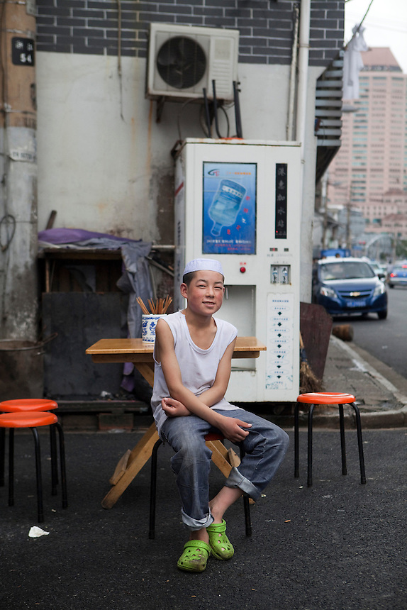 A young Hui, or Muslim boy works at a small restaurant in Shanghai.