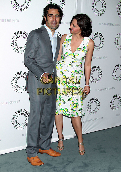 """Dario Franchitti, Ashley Judd.""""Missing"""" Premiere Screening presented by The Paley Center for Media held at The Paley Center For Media, Beverly Hills, California, USA..April 10th, 2012.full length white green print bird birds dress gold clutch bag grey gray suit profile  bending leaning .CAP/ADM/RE.©Russ Elliot/AdMedia/Capital Pictures."""