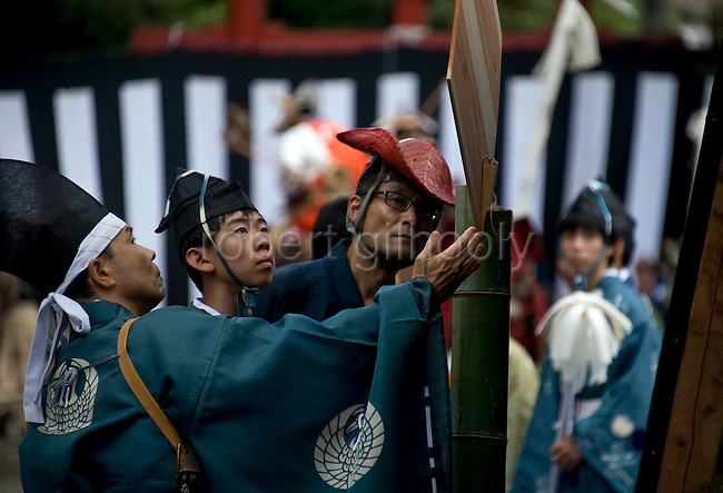 """Officials in traditional reset the wooden targets during the """"yabusame-shinji"""" mounted archery ritual on the 3-day Reitaisai grand festival in Kamakura, Japan on  16 Sept. 2012.  In the Azumakagami -- a book of Japanese history covering 87 years from 1180 to 1266 in the Kamakura Era, a hunt and mounted archery event was held on August 15 1187 and it is this in which the shrine's Reitaisai has its roots. For over 800 years since the history and tradition of the event have been continued at the shrine. Photographer: Robert Gilhooly"""