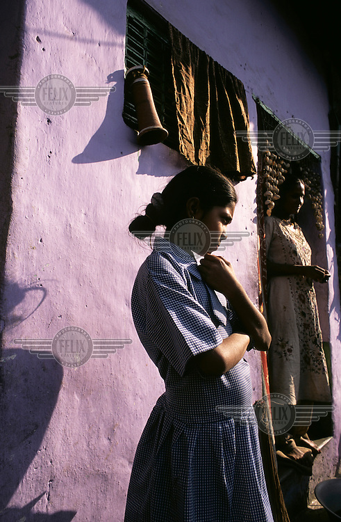 A girl stands outside her home in a slum area of Kolkata.
