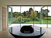 The circular black stone bath has a spectacular view of the garden through floor-to-ceiling windows