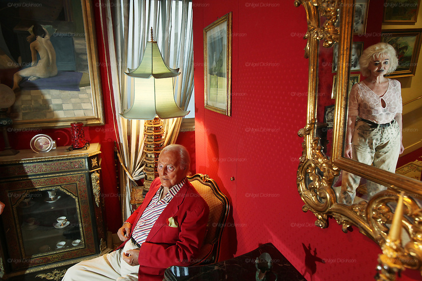 Wolf C Hartwig aged 91, producer of epic films and soft-porn features, with his fourth wife, and actress, Veronique Vendell in their apartment on Avenue de Foch, Paris. Wolf Hartwig was awarded a Bambi Award from German Cinema for his film 'The Iron Cross' which was directed by Sam Peckinpah starring James Coburn with Veronique Vendell. A producer working in exploitation genres, soft porn, sex, lurid, violent and sensational features. Other films he produced include 'Horrors from Spider Island'. 'Lady Hamilton' and 'Virgin of the Seven Seas'.//Veronique Vendell reflected in mirror and with Wolf Hartwig and painting of nude in vestibule