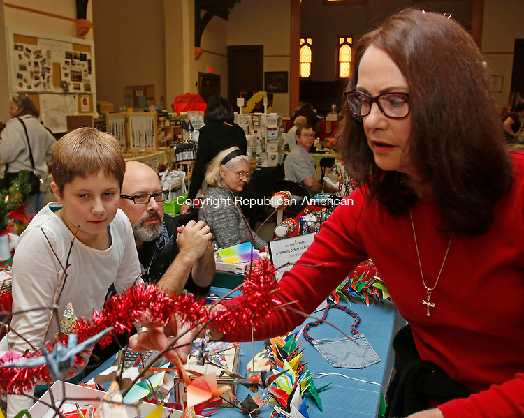 Torrington, CT-11 November 112115MK11 Robin Turpin (right) looks at Origami for sale created by (from left) parishiners Caroline and her dad Conrad Sienkiewicz, from Double C Crafts, during the Christmas Fair at Trinity Episcopal Church in Torrington Saturday afternoon.  Naomi Cardello, co-chair of the fundraising committee, said that twenty vendors participated in the yearly tradition to help raise funds for the church's capital campaign. Michael Kabelka / Republican-American
