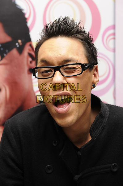 "GOK WAN.Singing copies of his new book ""How To Dress"" at Waterstone's in Bluewater, Kent, England, October 10th 2008..portrait headshot glasses black rimmed funny face winking eye .CAP/FIN.©Steve Finn/Capital Pictures"