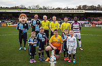 Captains Paul Hayes of Wycombe Wanderers & Andy Yiadom of Barnet pose with Referee Gavin Ward, officials & club mascots during the Sky Bet League 2 match between Wycombe Wanderers and Barnet at Adams Park, High Wycombe, England on 16 April 2016. Photo by Andy Rowland.
