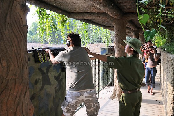 Asia, Vietnam, Cu Chi nr. Ho Chi Minh City (Saigon). Cu Chi Tunnels. Tourists enjoying themselves at a shooting gallery.