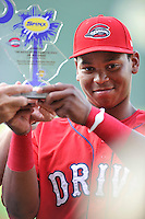 Third baseman Rafael Devers (13) of the Greenville Drive holds his player of the month award before a game against the Charleston RiverDogs on Friday, August 14, 2015, at Fluor Field at the West End in Greenville, South Carolina. Charleston won 6-2. (Tom Priddy/Four Seam Images)