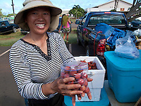 Woman holding a bag of lichee fruit at an open market