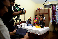 Members of 'Me N Ma Girls', Myanmar's first girl band, being filmed on a bed during a video shoot. The band's members were recruited by Australian dancer Nicole May. They sing and dance in the manner of many Western pop acts but in socially conservative Myanmar, they represent a radical break from the norm.