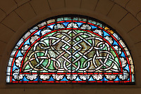 Stained glass window in a tympanum, with interlaced knot design, by Paul Abadie, 19th century, in Angouleme Cathedral, or the Cathedrale Saint-Pierre d'Angouleme, Angouleme, Charente, France. The 12th century Romanesque cathedral was largely reworked by Paul Abadie in 1852-75. In 2008, Jean-Michel Othoniel was commissioned by DRAC Aquitaine - Limousin - Poitou-Charentes to display the Treasure of the Cathedral in some of its rooms, which opened to the public on 30th September 2016. Picture by Manuel Cohen