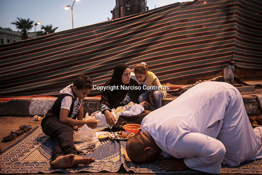 In this Thursday, Jul. 11, 2013 photo, a Muslim supporter of ousted president Mohammed Morsi offers prayers as his family await to break the fasting at the dusk in the Cairo University during the second day of the holy month of Ramadan in Cairo, Egypt. (Photo/Narciso Contreras).