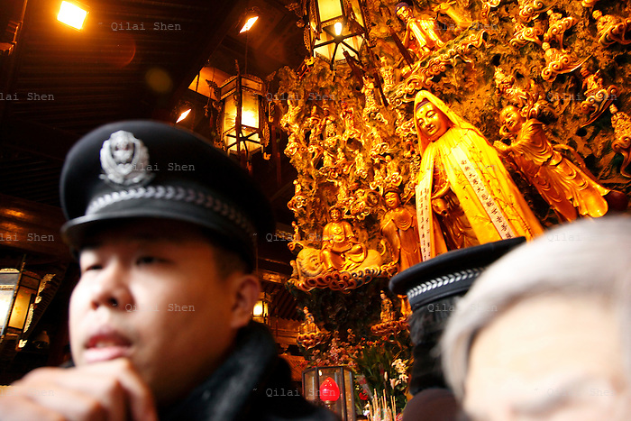 A policeman tries to manage throngs of worshippers at Longhua temple in Shanghai, China on 26 January, 2009.  Traditionally the first day of the lunar new year is an auspicious day to offer prayers and honor ancestors.