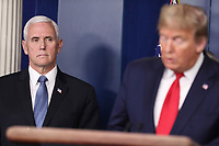 United States Vice President Mike Pence, left, listens as US President Donald J Trump speaks during a press conference with members of the coronavirus task force in the Brady Press Briefing Room of the White House on March 24, 2020 in Washington, DC.<br /> Credit: Oliver Contreras / Pool via CNP/AdMedia