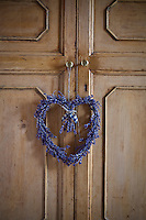 A heart made of dried lavender hangs on a cupboard door
