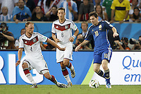 Lionel Messi of Argentina takes on Benedikt Howedes and Mesut Ozil of Germany