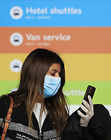 "BOGOTA, COLOMBIA - March 12:  A woman wears a face mask as she checks here phone at the International airport ""El Dorado"" on March 12, 2020 in Bogota, Colombia. The World Health Organization declared a global pandemic as the coronavirus rapidly spreads across the world. Colombian President Ivan Duque declared a health emergency to contain an outbreak of coronavirus, suspending public events with more than 500 people. (Photo by Daniel Munoz/VIEWpress)"
