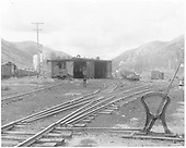 North end view of the Rico engine house with switching activity on the east side and a 3-way switch and harp stand in the foreground.<br /> RGS  Rico, CO  Taken by Gerbaz, Del H. - 1950