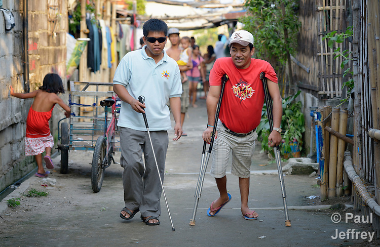 Dennis Garcia (left), president of the Abucay Federation of People With Disabilities in Abucay, Bataan, Philippines, talks with Florencio Fajardo, president of the local organization of people living with disabilities in Orani, a neighboring town.