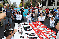 Phoenix, Arizona. April 25, 2012 - From left (on the ground): Danielle Nieto, Amy McMullen, Jovana Renteria, Jesse Davenport and Tony Verdugo (bottom corner), block Central Avenue as they protest against SB 1070. About 500 people protested the controversial law on the same day U.S. Supreme Court justices heard legal arguments on the Arizona vs. United States case. At the end of the march, six activists blocked Central Avenue by sitting in the middle of the street. They all were arrested by the Phoenix Police Department and taken to the Fourth Avenue County Jail. Photo by Eduardo Barraza © 2012