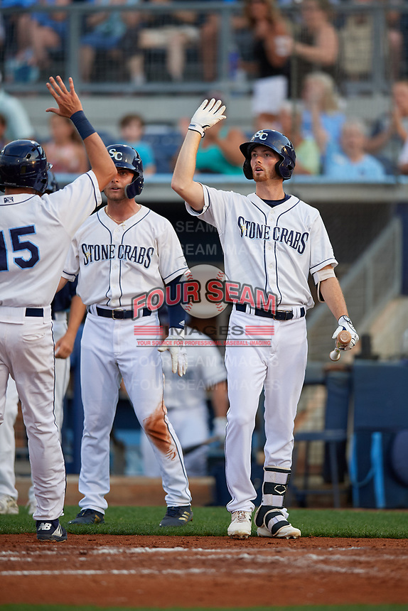 Charlotte Stone Crabs Tanner Dodson (10) and Zacrey Law (center) high five Zach Rutherford (15) after scoring a run during a Florida State League game against the Fort Myers Miracle on April 6, 2019 at Charlotte Sports Park in Port Charlotte, Florida.  Fort Myers defeated Charlotte 7-4.  (Mike Janes/Four Seam Images)