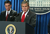 United States President George W. Bush speaks to the media as former Virginia governor and U.S. Senator Chuck Robb (Democrat of Virginia), left, listens February 6, 2004 at the briefing room of the White House in Washington, DC. President Bush appointed Robb and Judge Laurence Silberman (not pictured) to head a bipartisan commission that will investigate the Iraqi intelligence failures. <br /> Credit: Alex Wong / Pool via CNP