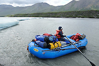 Georgia Bennett rows a raft past a stretch of river ice known as aufeis along the Hulahula River on a summer day in Alaska's Arctic National Wildlife Refuge. MR#001