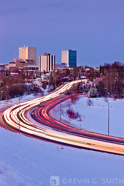 The downtown Anchorage Skyline overlooking Westchester Lagoon with traffic on Minnesota Blvd. at twilight, Winter, Southcentral Alaska, USA.
