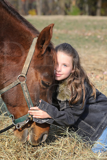 Young girl hugs her horse closely as it grazes hay, an affectionate and cute eight year old dressed in denim with long brunette hair.
