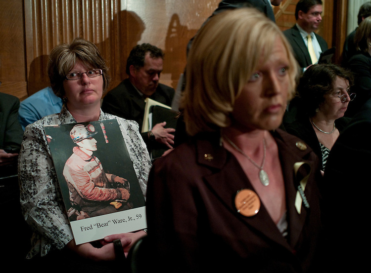"WASHINGTON, DC - April 27: Peggy Cohen, of Sago, W.Va., holds a picture of her father, Fred ""Bear"" Ware Jr., who was killed in the Sago Mine explosion in 2006, as she sits in the audience during the Senate Health, Education, Labor and Pensions Committee hearing on mine safety, and safety in other workplaces, in the wake of the disaster at Upper Big Branch mine in Montcoal, W.Va., that killed 29 workers this month. Saying that no one should die for a paycheck, the new head of the Mine Safety and Health Administration asked lawmakers Tuesday for additional authority to go after scofflaw mine owners, even as he vowed tougher enforcement under existing law. (Photo by Scott J. Ferrell/Congressional Quarterly)"