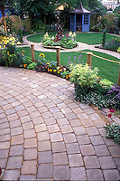 Brick pavered circular patio overlooking backyard with gazebo and garden beds and walkway