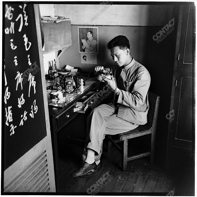 "Li checks his camera equipment in his office at the Heilongjiang Daily (photographed with a self-timer). The sign on the door reads, ""Read Chairman Mao's books and follow his instruction."" 27 May 1966"