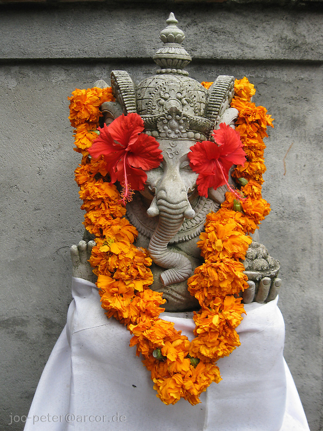Ganesha stone sculpture with flowers in entrance area of private home compound, Ubud, Bali, archipelago Indonesia
