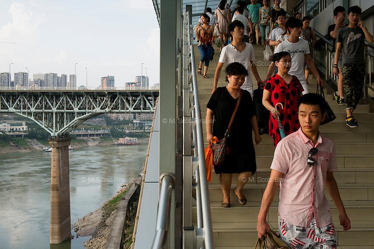 People walk down stairs to an elevated subway platform at the Niujiaotuo subway station in the Yuzhong district of Chongqing, China. Visible at left is the Chongqing Jialingjiang Bridge over the Jialing River.