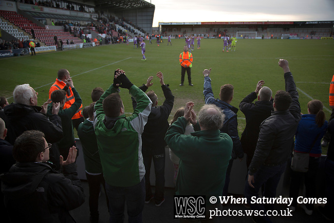 Morecambe 0 Plymouth Argyle 2, 25/03/2016. Globe Arena, League 2. Visiting fans celebrating their team's victory as Morecambe hosted Plymouth Argyle in a League 2 fixture at the Globe Arena. The stadium was opened in 2010 and replaced Morecambe's traditional home of Christie Park which had been their home since 1921, the year after their foundation. Plymouth won this fixture by 2-0 watched by 2,081 spectators, in a game delayed by 30 minutes due to traffic congestion affecting travelling Argyle fans.  Photo by Colin McPherson.