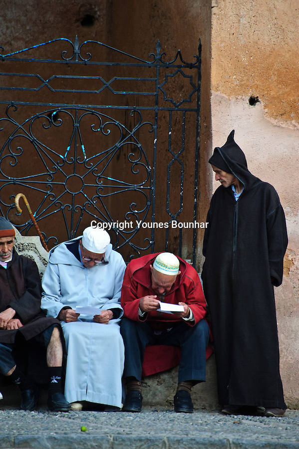 Elderly men sitting in the main plaza of Chefchaouen talking about the latest events