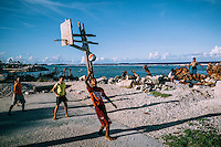 Children play basketball on a patch of waste ground beside the sea. It is one of the most popular sports among young people on the island. Several dozen makeshift basketball courts have been constructed on the island.