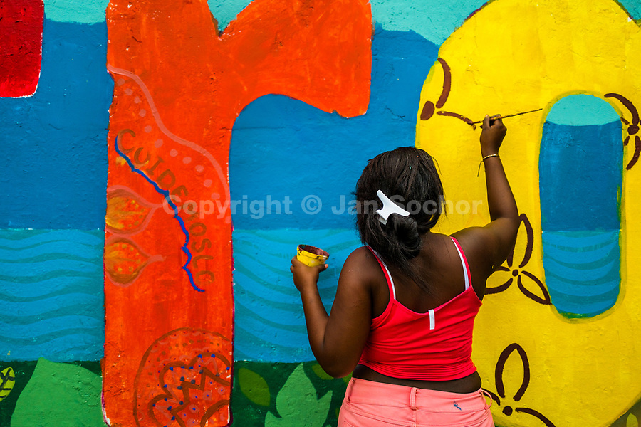 "An Afro-Colombian female student paints a society and environment-related mural on a school wall in Quibdó, Colombia, 5 October 2019. Supervised by a Bogotan street artist named Guache, a group of young activists from Chocó department created a large artwork called ""Somos Atrato"" (""We are [the river] Atrato"") celebrating the Afro-Colombian heritage and accenting the inherent link between the communities and the river Atrato in the Pacific region of Colombia."