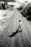 Man walking across country road