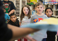 NWA Democrat-Gazette/CHARLIE KAIJO Second grade students look on as DJ Bobo (left) holds up recycled paper during an art class, Monday, December 3, 2018 at Russell D. Jones in Rogers.<br />