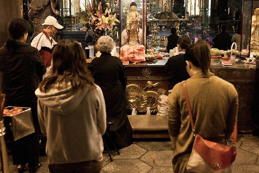 Prière silencieuse dans la foule pour ces jeunes fidèles du temple bouddhique de Longshan, l'un des plus anciens de Taipeh. Le temple rese ouvert jusqu'à 22 heures.