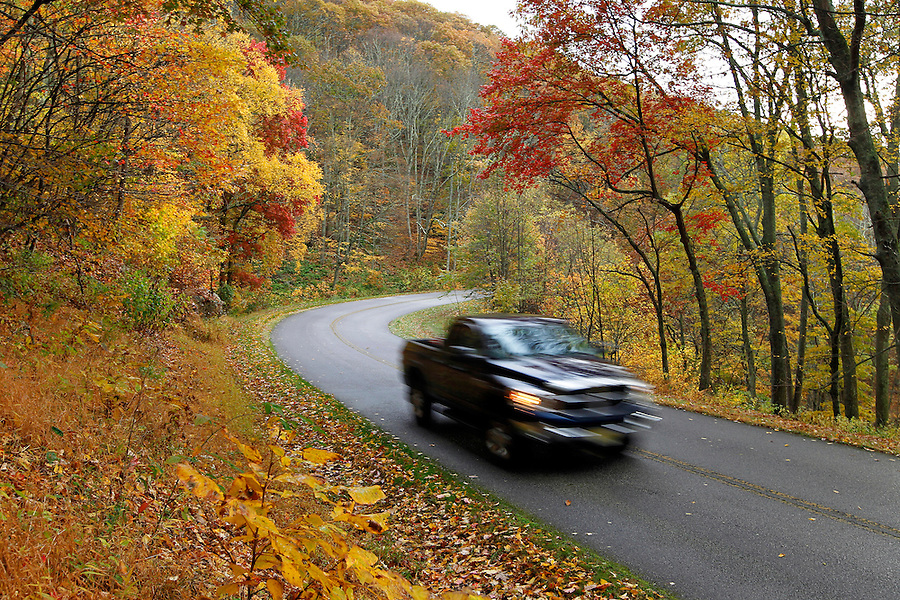 A truck rides past fall colored trees on the Blue Ridge Parkway in Nelson County, Va. Photo/Andrew Shurtleff
